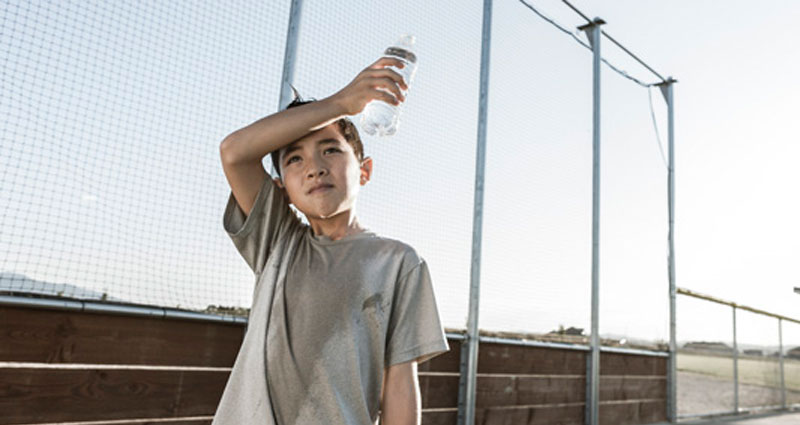 child sweating and holding bottle of water