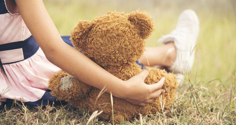 child holding stuffed animal