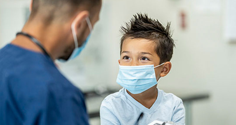 child in face mask speaking with medical professional